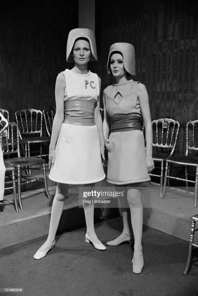 Two sleeveless belted dresses by Pierre Cardin at a fashion show, 1967. They are worn with helmet-style hats.