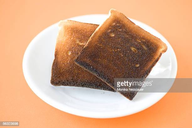 Two slices of  burned toast on plate, close-up, elevated view