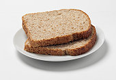 Two slices of whole-wheat bread on a plate, studio shot