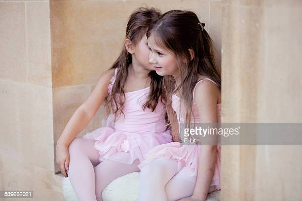 Two small ballet dancers (4-5) in pink clothes sitting by stone wall