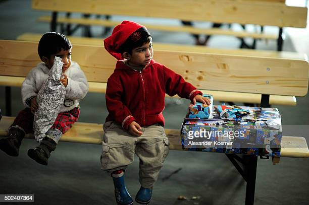 Two small boys watch other children unpacking presents given by a volunteer dressed as Santa Claus at a shelter for migrants and refugees on December...