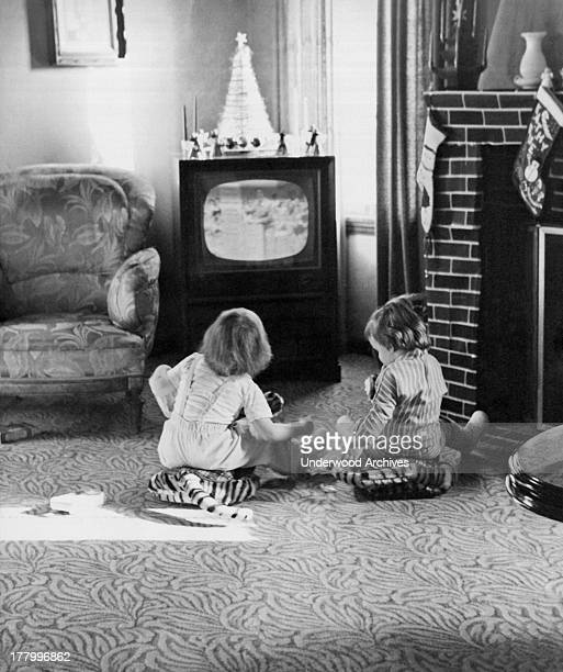 Two small children sitting on the living room floor watching television c 1955