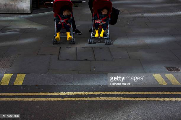 Two small children sleep in their respective buggies as unseen parents prepare to cross a street in the City of London We see the repetition of...