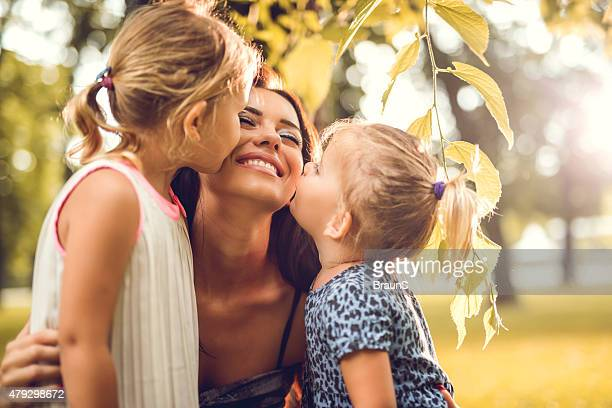 Two small daughters kissing their mother in nature.