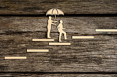 Two small people silhouette walking up stairway as one holds an umbrella over the other as they walk over wood background.