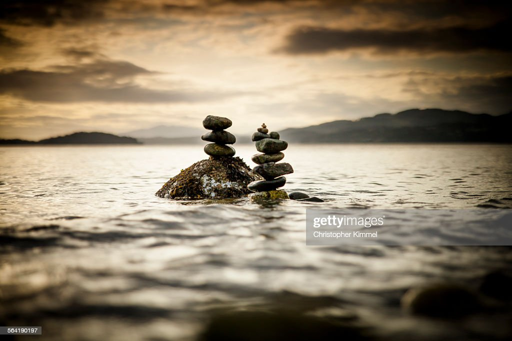 Two small rock stacks are built near the shore of a beach in Sechelt, Canada.