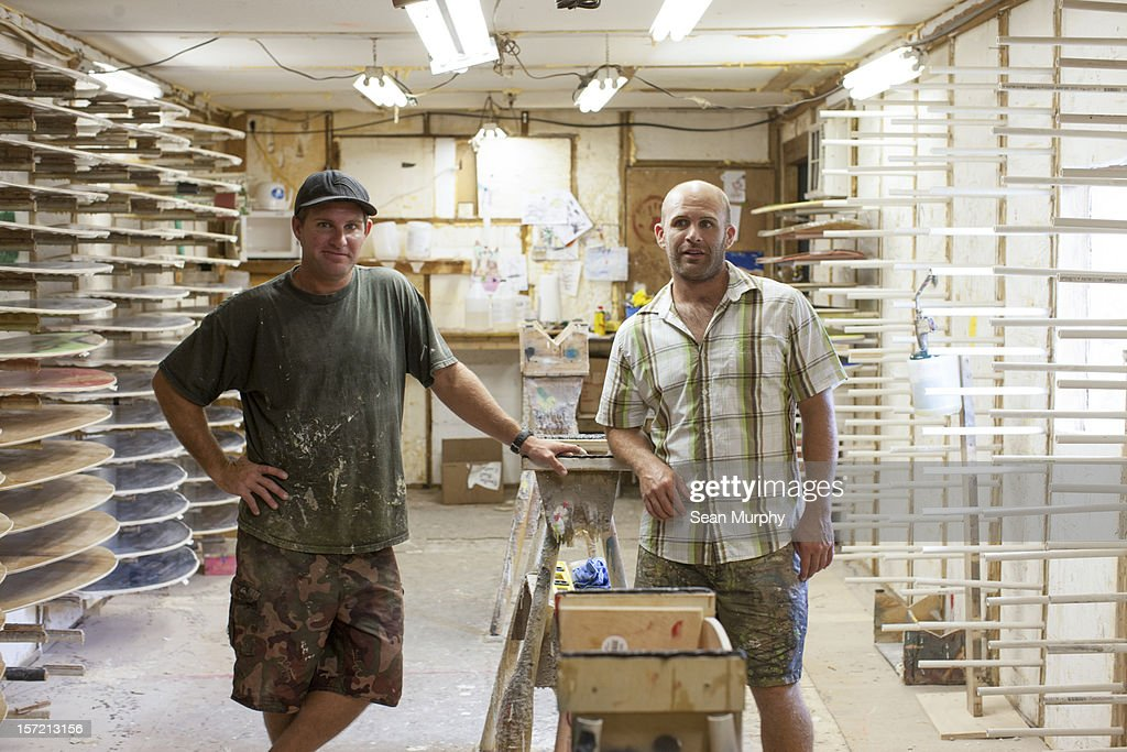 Two small shop owners standing inside a surf shop : Stock Photo