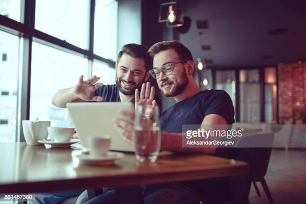 Two Smiling Brothers Video Conferencing in Nice Cafe Restaurant
