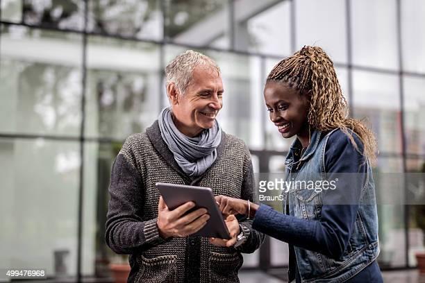 Zwei lächelnden Kollegen Arbeiten auf tablet PC im Freien.