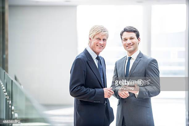 Two smiling businessman with digital tablet