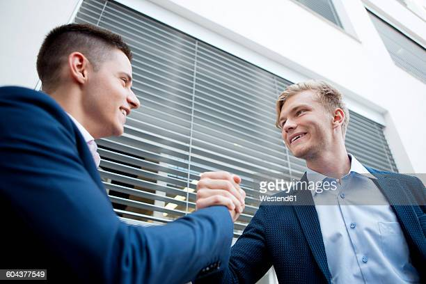 Two smiling businessmen shaking hands outdoors