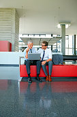 Two smiling businessmen working on laptop in office lobby