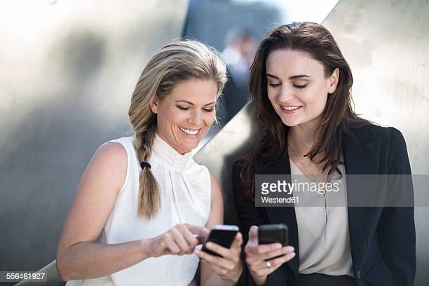 Two smiling businesswomen looking at cell phones