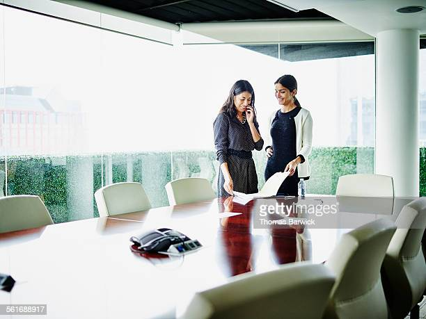 Two smiling businesswomen reviewing documents