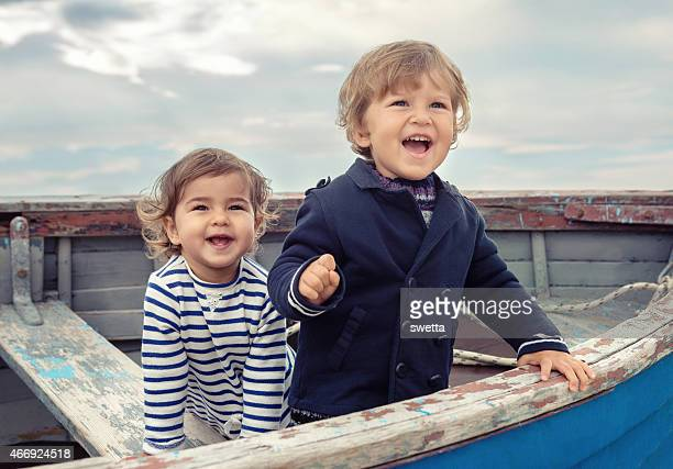 Two smiling children playing in a worn rowboat