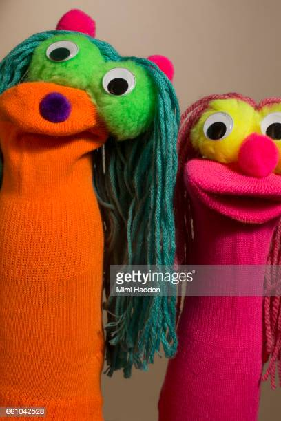 Two Smiling Colorful Sock Puppets on Neutral Seamless