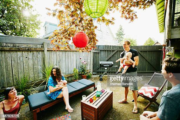 Two smiling couples with babies having barbecue