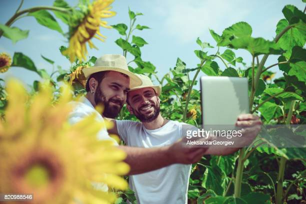 Two Smiling Farmers Making Selfie with Digital Tablet in Sunflower Field