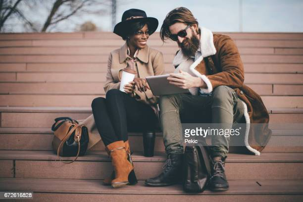 Two smiling friends using digital tablet