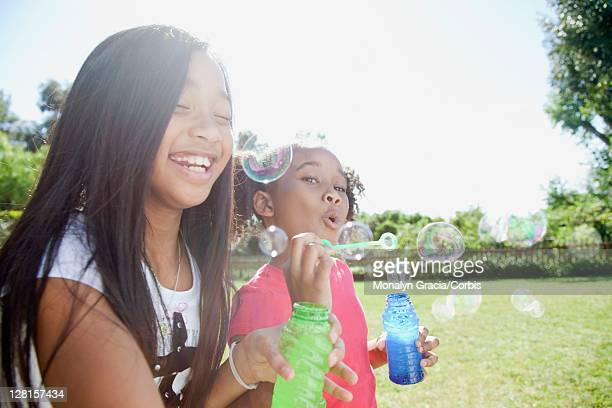 Two smiling girls (10-12) blowing bubbles outdoors