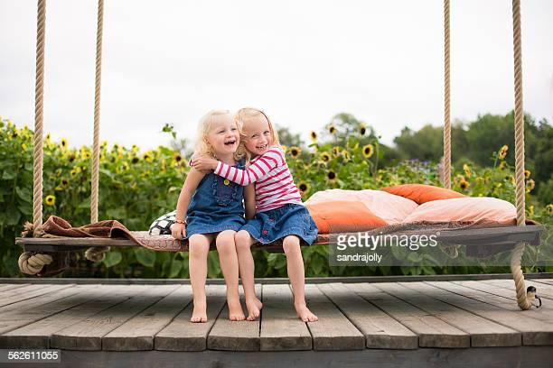 Two smiling girls sitting on a swing bed