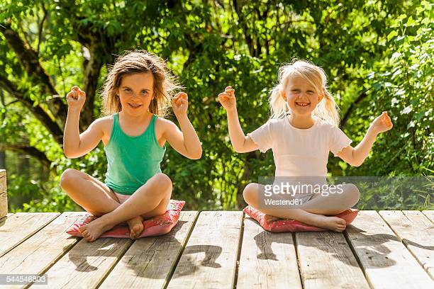 Two smiling girls sitting on wooden terrace