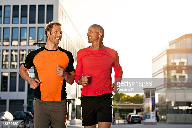 Two smiling joggers running in city