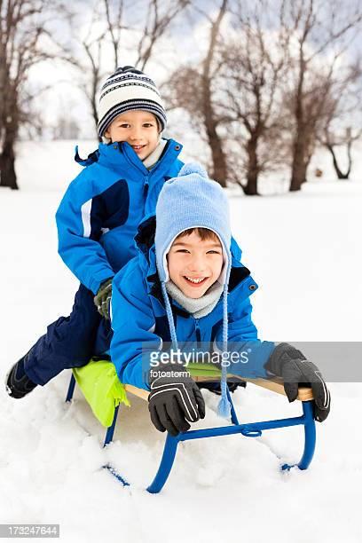Deux petits garçons, souriant de la luge dans la neige
