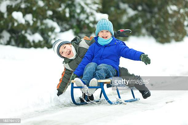 Two smiling little boys sledding in snow