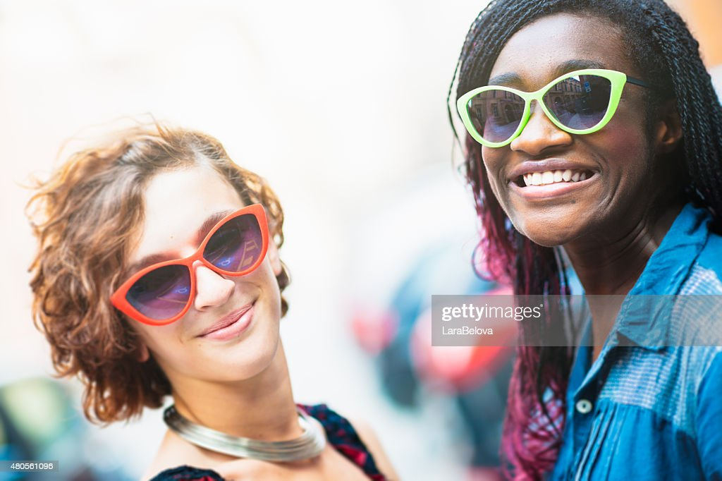 Two smiling mixed race girlfriends on the street : Stock Photo