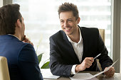 Two smiling positive businessmen discussing new project at meeting, joking and laughing, friendly nice manager consulting client, business partners having fun during discussion, good relationships