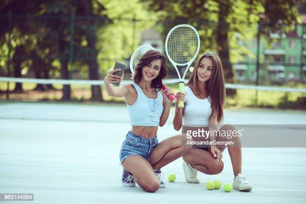 Two Smiling Sensual Female Friends Taking Selfie on Tennis Court