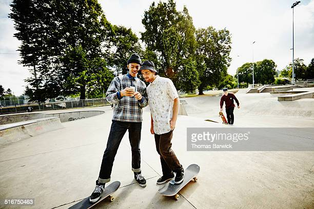 Two smiling skateboarders looking at smartphone