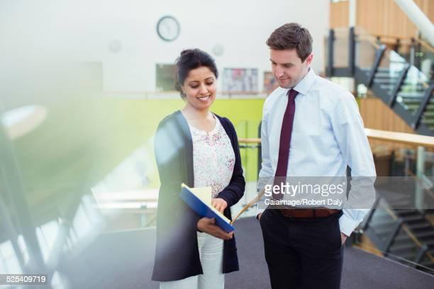 Two smiling teachers talking in corridor in high school
