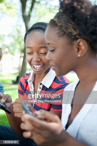 Two Smiling Teen Girls Outdoors with Smart Phones : Stock Photo