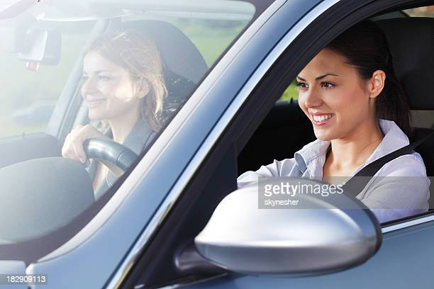 Two smiling women drive a car.