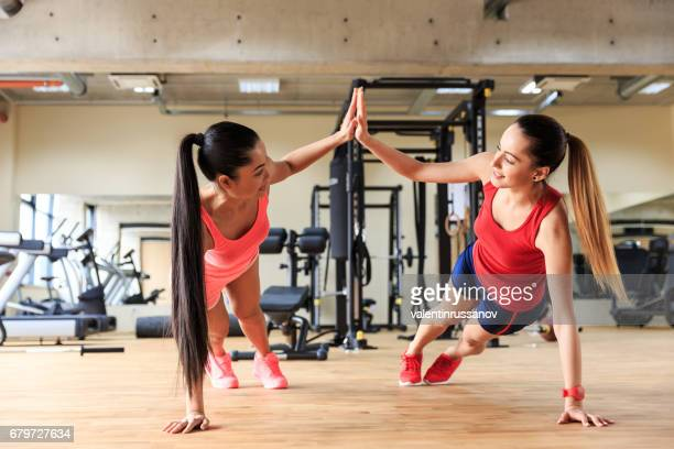 Two smiling women practicing in gym together