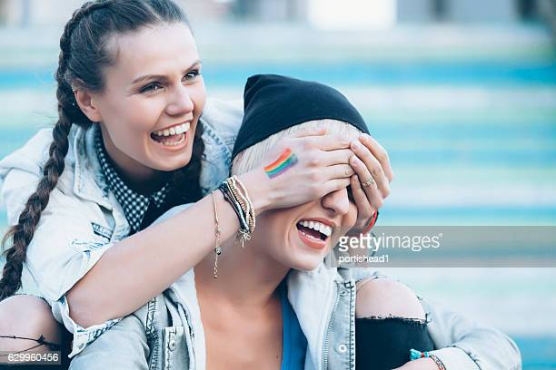 Two smiling women sitting on colorful stairs and having fun