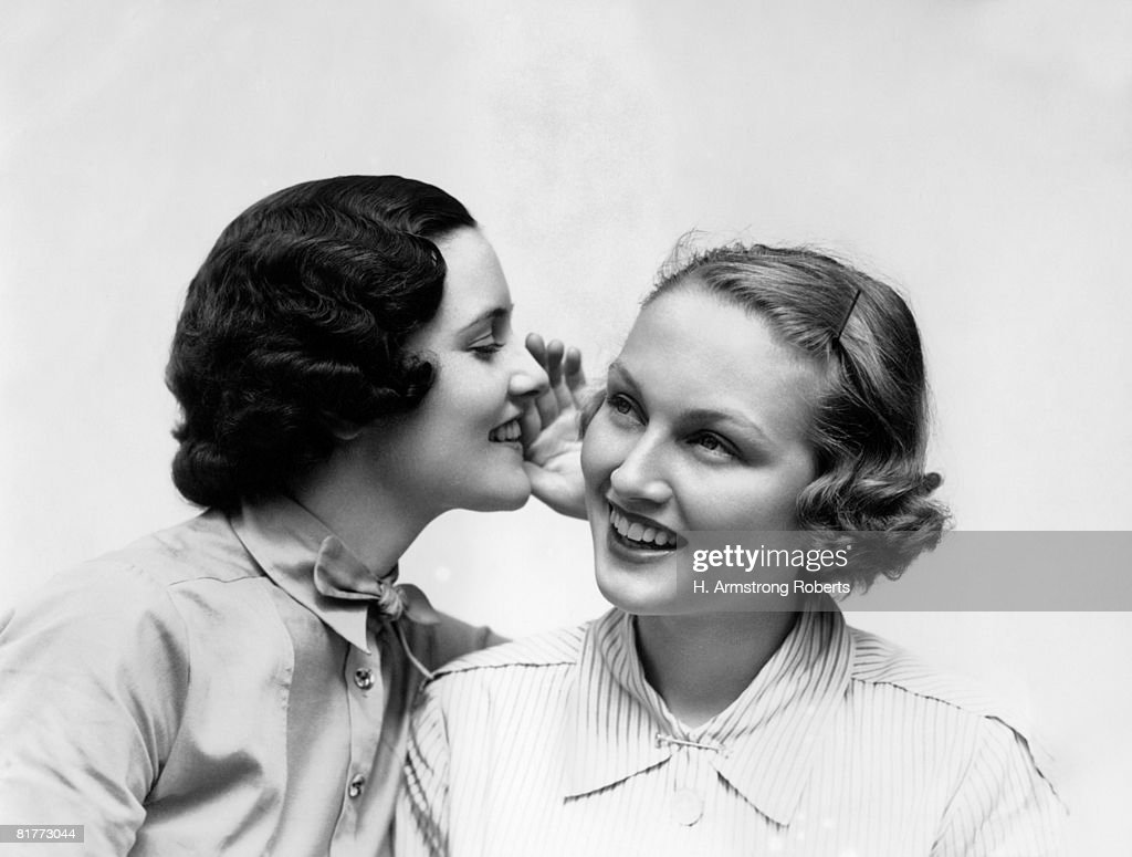 Two Smiling Women The 1 Wearing The Blouse With A Bowtie Is Wispering A Secret In The Ear Of The I Wearing A Shirt & Collar Pin Blonde Teeth. : Stock Photo