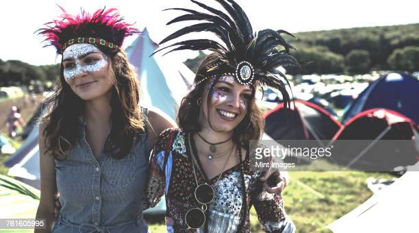 Two smiling young women at a summer music festival face painted, wearing feather headdress, standing among tents.