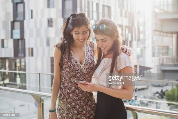 Two smiling young women looking at cell phone in the city