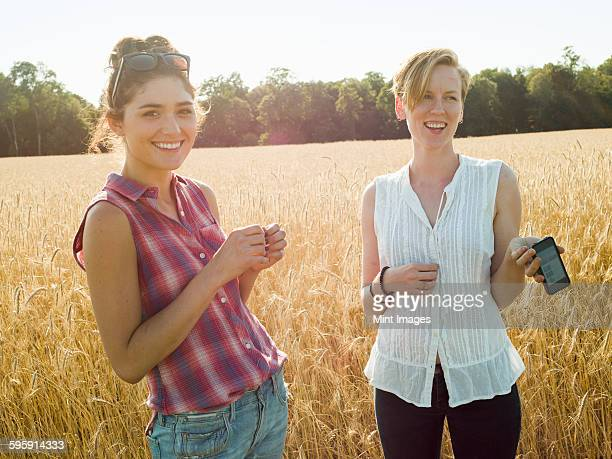 Two smiling young women standing in a cornfield, one holding a smart phone.