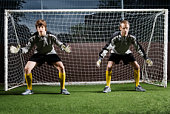 Two soccer players defending football goal