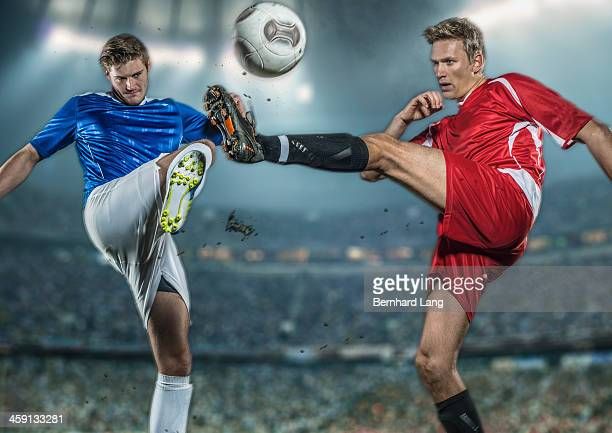 Two soccer players fighting for ball in stadium
