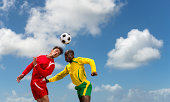 Two soccer players challenge for the ball during a match