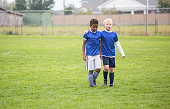 Soccer teammates consoling each other after a tough loss on a soccer field. One boy putting his arm around his friend as they walk off the grassy field. Concept photo of encouragement from friends aft