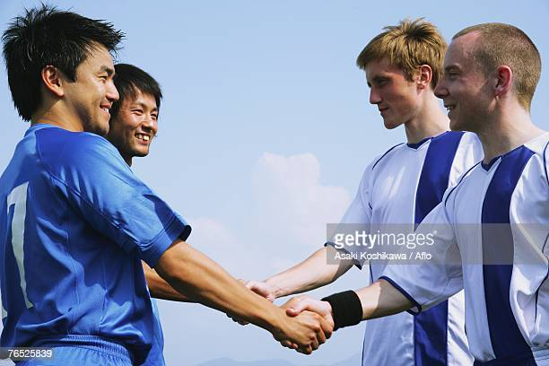Two soccer teams shake hands