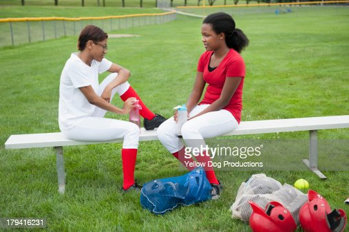 Two Softball Teammates sitting on Bench Together : Stock Photo