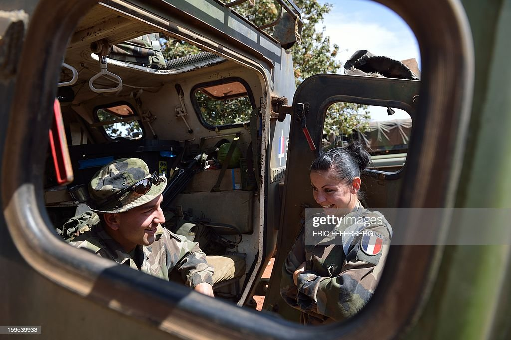 Two soldiers discuss as French troops with armourded vehicles from the 'Licorne' operation based in Abidjan (Ivory Coast) prepare their material at the 101 military airbase near Bamako on January 15, 2013. French President Francois Hollande said on Tuesday that his government does not intend to keep forces in Mali, but will remain until security is restored and 'terrorists' eliminated. Hollande said the intervention was aimed at ending attacks by Islamists, securing the capital and restoring the territorial integrity of the west African nation. FEFERBERG