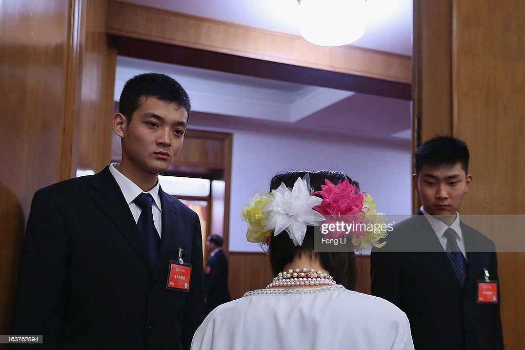 Two soldiers dressed as ushers check the pass of an ethnic minority delegate at the enterance of the meeting room for the fifth plenary meeting of the National People's Congress at the Great Hall of the People on March 15, 2013 in Beijing, China. Li Keqiang was elected as China's Premier Friday at the 12th National People's Congress, the country's top legislature.